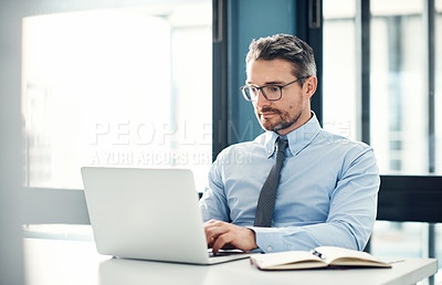 Buy stock photo Shot of a mature businessman using a laptop at his desk in a modern office