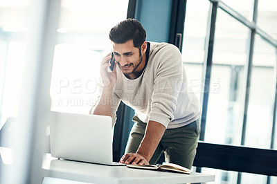 Buy stock photo Shot of a young businessman using a laptop and mobile phone at his desk in a modern office