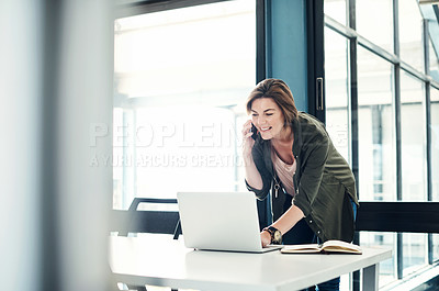 Buy stock photo Shot of a young businesswoman using a laptop and mobile phone at her desk in a modern office