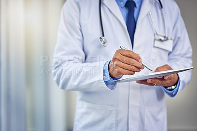 Buy stock photo Shot of an unrecognizable male doctor writing on a digital tablet while standing inside of a hospital during the day