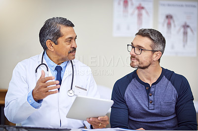 Buy stock photo Shot of a confident mature male doctor seated at his desk while consulting a patient inside a hospital during the day