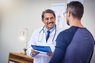 Buy stock photo Shot of a cheerful mature male doctor consulting a patient while standing inside a hospital during the day