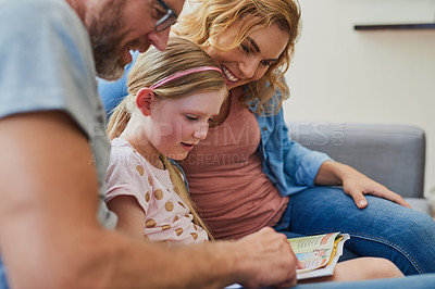 Buy stock photo Cropped shot of a mother and father reading a book with their daughter on the sofa at home