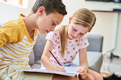 Buy stock photo Cropped shot an adorable brother and sister doing schoolwork together on the sofa at home