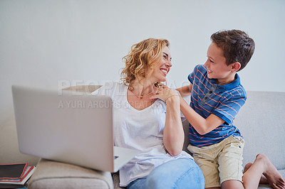 Buy stock photo Cropped shot of a mother using a laptop while her son surprises her on the sofa at home