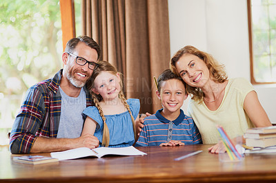 Buy stock photo Cropped shot of an affectionate family doing schoolwork together at home