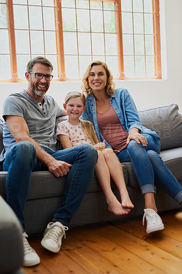 Buy stock photo Shot of a mother and father with their adorable daughter on the sofa in the living room at home