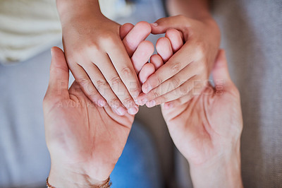 Buy stock photo High angle shot of a mother and son holding hands at home