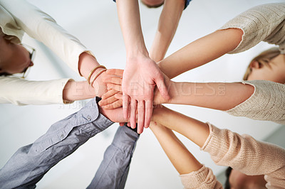 Buy stock photo Low angle shot of a group of coworkers joining their hands  together in a huddle