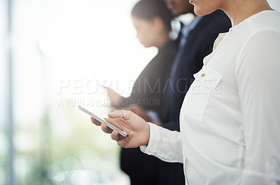 Buy stock photo Cropped shot of a group of unrecognizable businesspeople using their cellphones while standing in a row