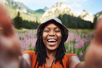 Buy stock photo Cropped shot of an attractive young woman taking a selfie in a field of flowers in nature