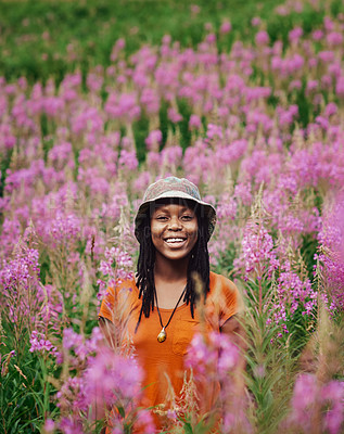 Buy stock photo Cropped shot of an attractive young woman standing in a field of flowers in nature