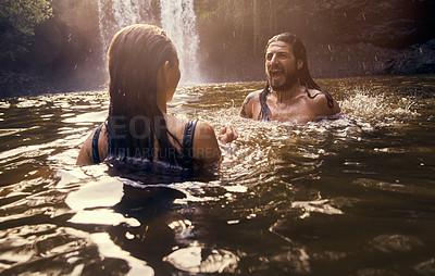 Buy stock photo Shot of a young couple swimming together in a lake
