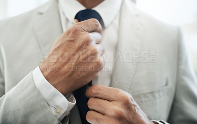 Buy stock photo Shot of an unrecognizable businessman wearing a business suit while adjusting his tie before going out to work at home during the day