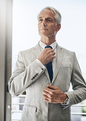 Buy stock photo Shot of a confident mature businessman wearing a business suit while adjusting his tie before going out to work at home during the day