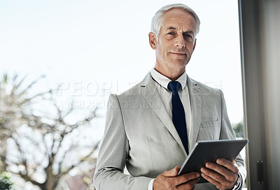 Buy stock photo Portrait of a confident mature businessman wearing a business suit while browsing on a digital tablet at home during the day