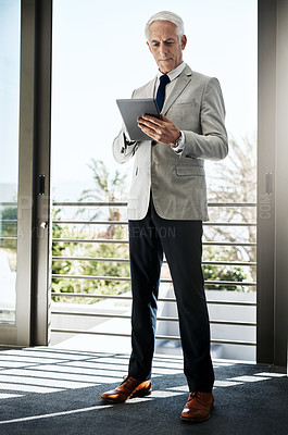 Buy stock photo Shot of a confident mature man wearing a business suit while browsing on a digital tablet at home during the day