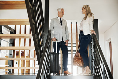Buy stock photo Shot of two confident businesspeople walking down stairs together while talking inside a building during the day