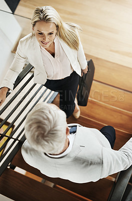 Buy stock photo High angle shot of two confident businesspeople having a chat while standing on a staircase inside a house during the day