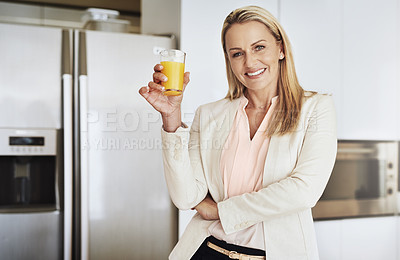 Buy stock photo Portrait of a cheerful middle aged businesswoman enjoying a glass of orange juice in the kitchen during the day