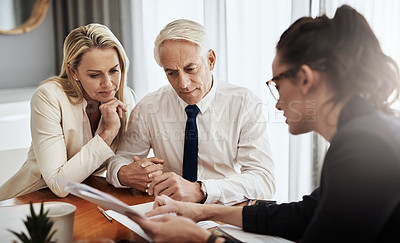 Buy stock photo Shot of a focused mature couple negotiating with a architect over house plans around a table inside of a building during the day