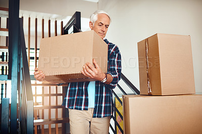 Buy stock photo Shot of a handsome mature man carrying a box on moving day