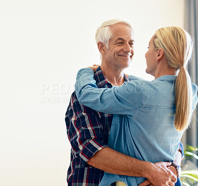 Buy stock photo Shot of an affectionate mature couple embracing at home