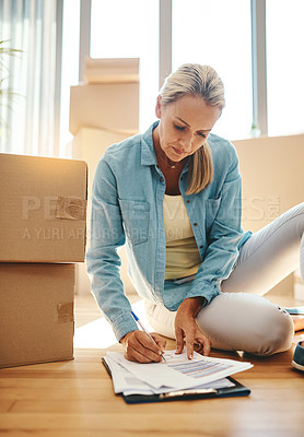 Buy stock photo Shot of a mature woman going through paperwork on moving day