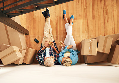 Buy stock photo High angle shot of a mature couple relaxing together with wine on moving day