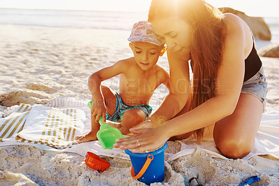 Buy stock photo Shot of a mother building sandcastles with her little son at the beach