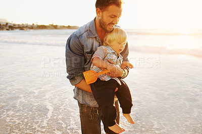 Buy stock photo Shot of a young man and his adorable son having fun at the beach