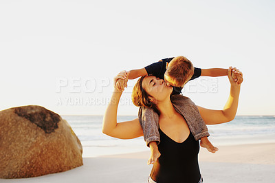 Buy stock photo Shot of an affectionate young woman carrying her son on her shoulders during a fun day at the beach