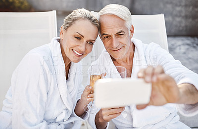 Buy stock photo Shot of a cheerful middle aged couple taking a self portrait together while enjoying a glass of champagne outside at a spa during the day