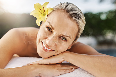 Buy stock photo Portrait of a cheerful middle aged woman lying on her stomach waiting to get a massage at a spa outside during the day