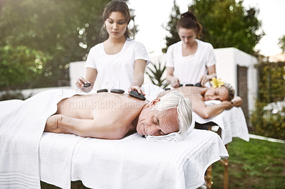 Buy stock photo Shot of a middle aged couple having a relaxing massage together at a spa during the day