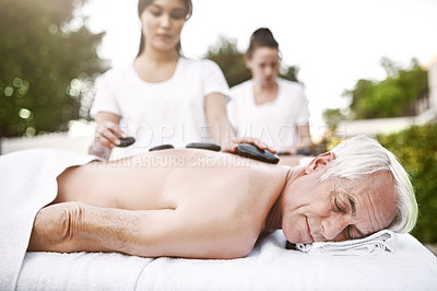 Buy stock photo Shot of a relaxed middle aged man lying on his stomach while receiving a massage at a spa outside during the day
