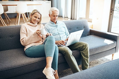 Buy stock photo Shot of mature couple using a laptop on the sofa at home