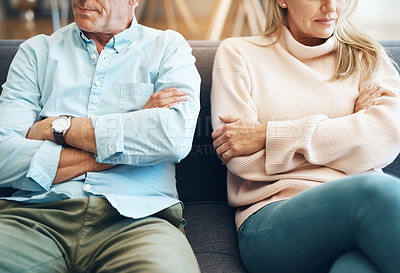 Buy stock photo Cropped shot of an unrecognizable mature couple sitting on the sofa with their arms folded after an argument