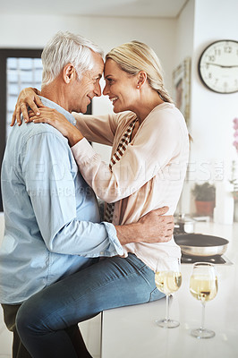 Buy stock photo Cropped shot of an affectionate mature couple sharing an intimate moment in their kitchen