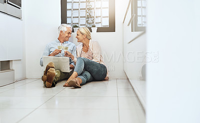 Buy stock photo Full length shot of an affectionate mature couple drinking wine while browsing the web on their kitchen floor