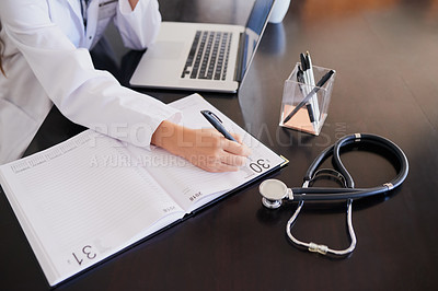 Buy stock photo High angle shot of an unrecognizable female doctor making notes while working in a hospital