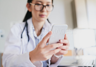 Buy stock photo Cropped shot of a young female doctor sending a text while working in the hospital