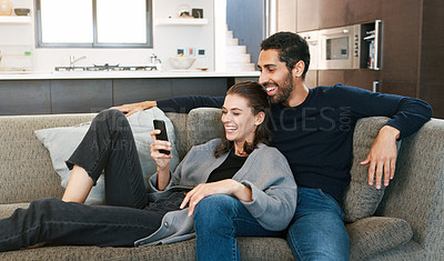 Buy stock photo Shot of a happy young couple using a cellphone while relaxing together at home