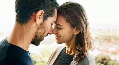 Buy stock photo Shot of an affectionate young couple standing face to face outdoors