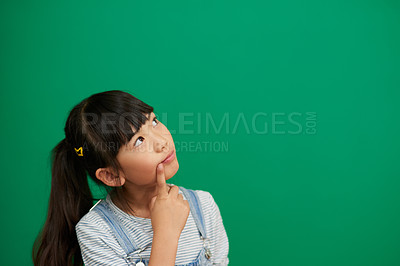 Buy stock photo Studio shot of an adorable little girl standing and contemplating against a green background