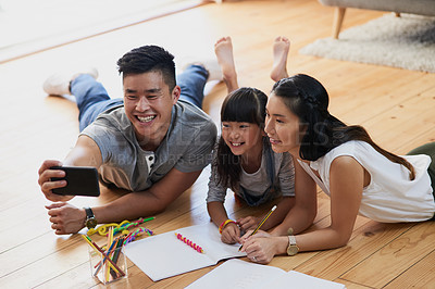 Buy stock photo Shot of a cheerful mother and father doing homework with their little girl while taking a self portrait at home during the day