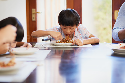 Buy stock photo Shot of a little boy enjoying a meal with his family at home