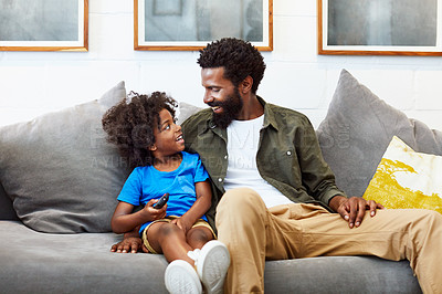 Buy stock photo Shot of a cheerful young father and son relaxing on a couch while watching television at home