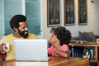 Buy stock photo Shot of a cheerful young father and son browsing on a laptop while having a cup of coffee in the kitchen at home