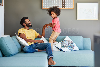 Buy stock photo Shot of a cheerful little boy trying to pull his father's arm to make him get up from a couch at home